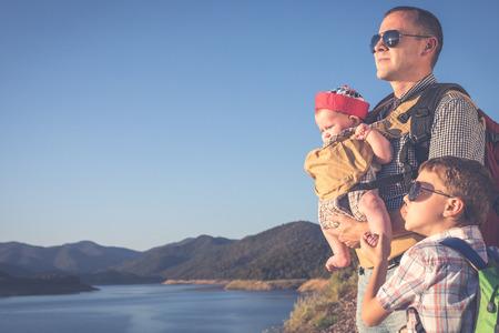 日中は湖の近くに立っている幸せな家族。フレンドリーな家族のコンセプト。
