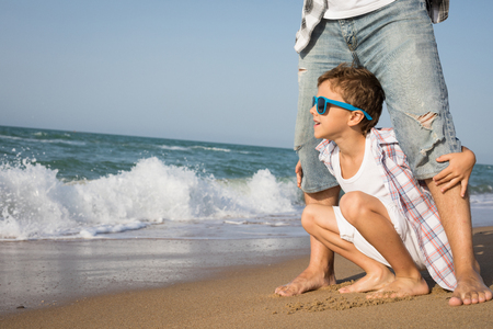 Father and son playing on the beach at the day time. People having fun outdoors. Concept of summer vacation and friendly family. Stockfoto
