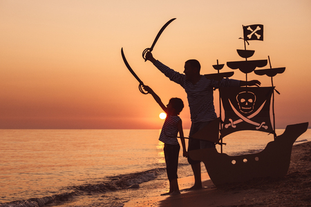 Father and son playing on the beach at the sunset time. They playing with a cardboard pirate ship. People having fun outdoors. Concept of summer vacation and friendly family.