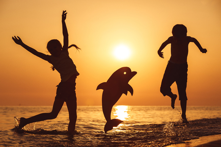 Happy little boy and girl jumping on the beach at the sunset time. They playing with a cardboard dolphin.  Kids having fun outdoors. Concept of summer vacation. Stock Photo