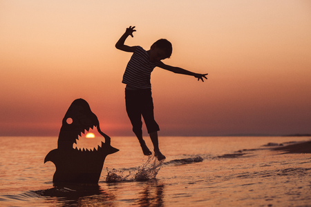 One happy little boy jumping on the beach at the sunset time. He playing with a cardboard shark.  Kid having fun outdoors. Concept of summer vacation. Stock Photo