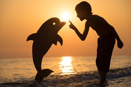 One happy little boy standing on the beach at the sunset time. He playing with a cardboard dolphin.  Kid having fun outdoors. Concept of summer vacation.