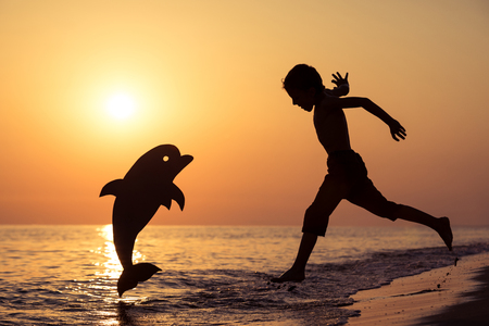 One happy little boy running on the beach at the sunset time. He playing with a cardboard dolphin.  Kid having fun outdoors. Concept of summer vacation.