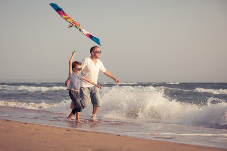 Father and son playing on the beach at the day time. People having fun outdoors. Concept of summer vacation and friendly family. Archivio Fotografico