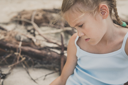 Portrait of one sad little girl. Child sitting on the beach at the day time. Concept of sorrow. 版權商用圖片