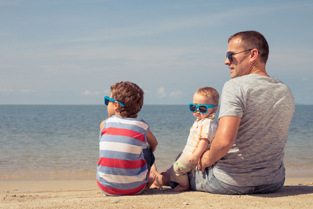 Father and  children playing on the beach at the summer day time. People having fun outdoors. Concept of summer vacation and friendly family.