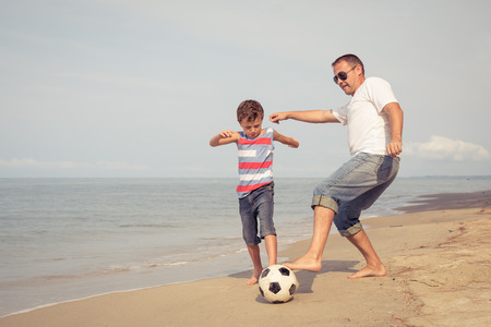 Father and son playing football on the beach at the summer day time. People having fun outdoors. Concept of friendly family.