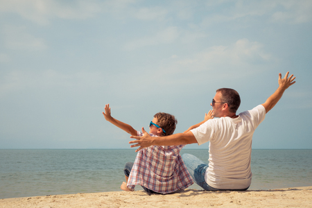 Father and  son playing on the beach at the day time. People having fun outdoors. Concept of summer vacation and friendly family.