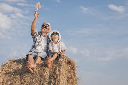 Vader en zoon spelen in het park op het moment van de dag. Mensen hebben plezier buitenshuis. Concept van zomervakantie en vriendelijke familie.