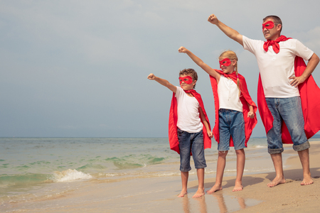 Father and children playing superhero on the beach at the day time. People having fun outdoors. Concept of summer vacation and friendly family.