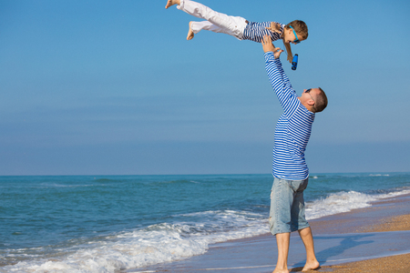Father and son playing on the beach at the day time. They are dressed in sailors vests. Concept of sailors on vacation and friendly family.