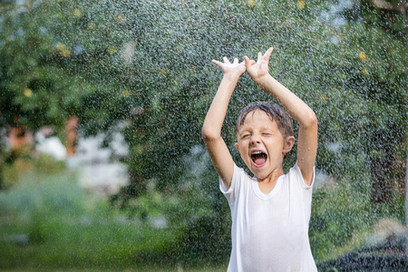 Happy little boy pouring water from a hose. Concept Brother And Sister Together Forever