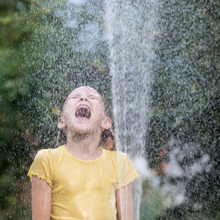 Happy little girl pouring water from a hose. Concept Brother And Sister Together Forever