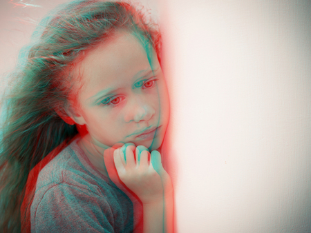 Portrait of sad blond little girl sitting outdoors near a  wall  at the day time. Concept of sadness. Glitched style photo.