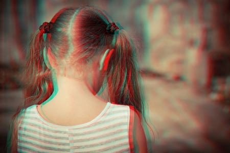 Portrait of sad blond little girl standing outdoors at the day time. Concept of sadness. Glitched style photo.