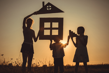 Happy children standing on the field at the sunset time. They build a house. Concept of friendly family. Reklamní fotografie