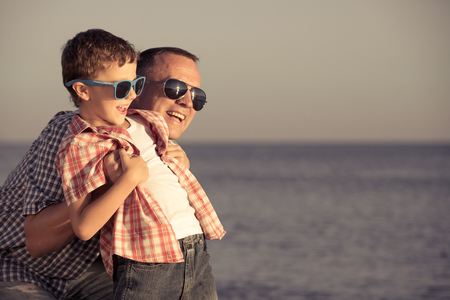 Father and son playing on the beach at the day time. People having fun outdoors.  Concept of happy vacation and friendly family. Standard-Bild - 116774178