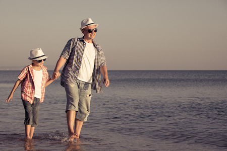 Father and son playing on the beach at the day time. People having fun outdoors.  Concept of happy vacation and friendly family. Standard-Bild - 116774179
