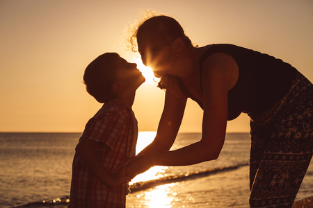 Mother and son playing on the beach at the sunset time. People having fun outdoors.  Concept of happy vacation and friendly family. Standard-Bild - 116774180
