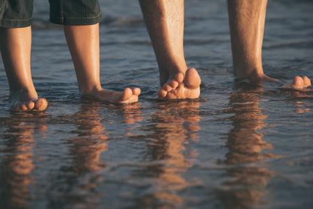 Vater und Sohn spielen tagsüber am Strand. Leute, die Spaß im Freien haben. Konzept des glücklichen Urlaubs und der freundlichen Familie. Standard-Bild