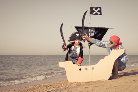 Father and son playing on the beach at the day time. They are dressed in sailor's vests and pirate costumes. Concept of happy game on vacation and friendly family. Standard-Bild - 116774192