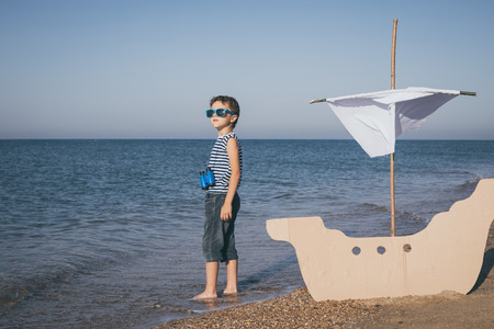 One happy little boy playing on the beach at the day time. He are dressed in sailor's vest. Kid having fun outdoors. Concept of sailor on vacation. Standard-Bild - 116774185