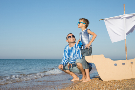 Father and son playing on the beach at the day time. They are dressed in sailor's vests. Concept of sailors on vacation and friendly family. Standard-Bild - 116774186