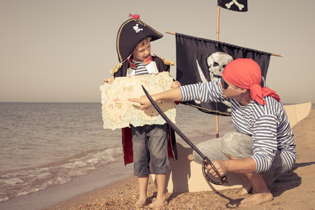 Father and son playing on the beach at the day time. They are dressed in sailor's vests and pirate costumes. Concept of happy game on vacation and friendly family. Standard-Bild - 116774187