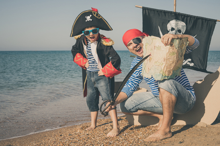 Father and son playing on the beach at the day time. They are dressed in sailor's vests and pirate costumes. Concept of happy game on vacation and friendly family. Standard-Bild - 116774189