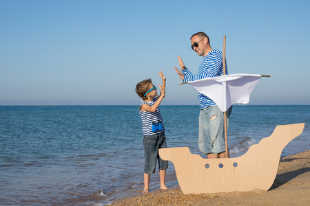 Father and son playing on the beach at the day time. They are dressed in sailor's vests. Concept of sailors on vacation and friendly family. Standard-Bild - 116774194
