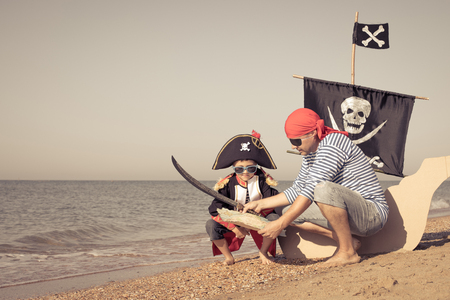 Father and son playing on the beach at the day time. They are dressed in sailor's vests and pirate costumes. Concept of happy game on vacation and friendly family. Standard-Bild - 116774197