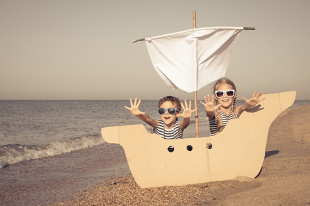 Happy children playing on the beach at the day time. Two Kids having fun outdoors. Concept of summer vacation and friendly family. Standard-Bild - 116774204