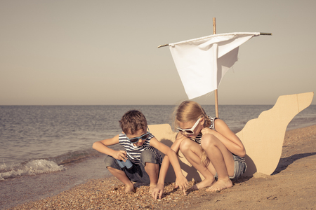 Happy children playing on the beach at the day time. Two Kids having fun outdoors. Concept of summer vacation and friendly family. Standard-Bild - 116774220