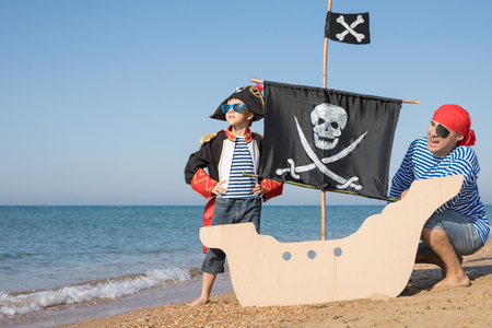 Father and son playing on the beach at the day time. They are dressed in sailor's vests and pirate costumes. Concept of happy game on vacation and friendly family. Standard-Bild - 116775420