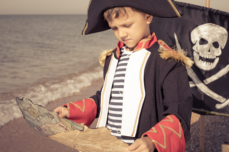 One happy little boy playing on the beach at the day time. He are dressed in pirate costume. Kid having fun outdoors. Concept of sailor on vacation. Standard-Bild - 116775429
