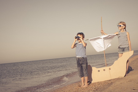 Happy children playing on the beach at the day time. Two Kids having fun outdoors. Concept of summer vacation and friendly family. Standard-Bild - 116775435