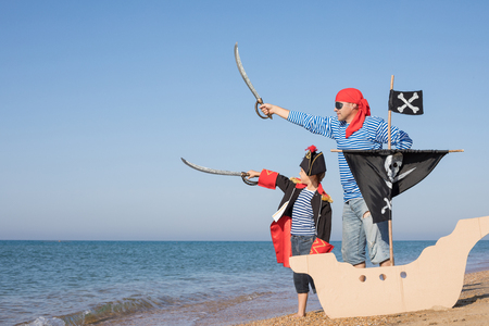 Father and son playing on the beach at the day time. They are dressed in sailor's vests and pirate costumes. Concept of happy game on vacation and friendly family. Standard-Bild - 116775437