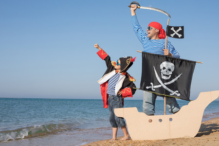Father and son playing on the beach at the day time. They are dressed in sailors vests and pirate costumes. Concept of happy game on vacation and friendly family.