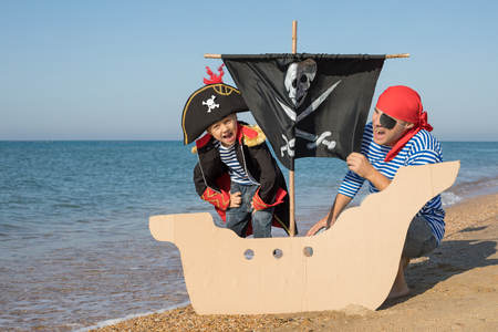 Father and son playing on the beach at the day time. They are dressed in sailor's vests and pirate costumes. Concept of happy game on vacation and friendly family. Standard-Bild - 116775442