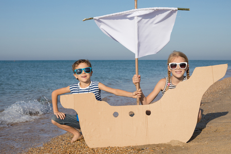 Happy children playing on the beach at the day time. Two Kids having fun outdoors. Concept of summer vacation and friendly family. Standard-Bild - 116775444