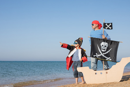 Father and son playing on the beach at the day time. They are dressed in sailor's vests and pirate costumes. Concept of happy game on vacation and friendly family. Standard-Bild - 116775447