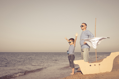 Father and son playing on the beach at the day time. They are dressed in sailor's vests. Concept of sailors on vacation and friendly family. Standard-Bild - 116775450
