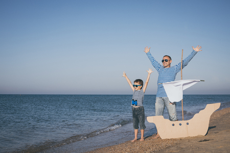 Father and son playing on the beach at the day time. They are dressed in sailor's vests. Concept of sailors on vacation and friendly family. Standard-Bild - 116775451