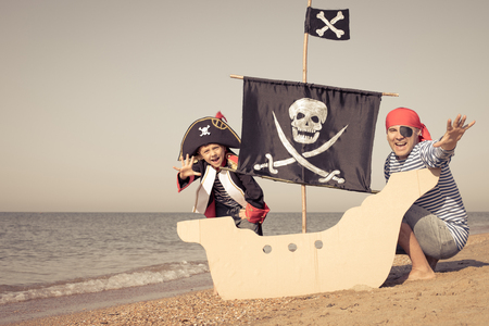 Father and son playing on the beach at the day time. They are dressed in sailor's vests and pirate costumes. Concept of happy game on vacation and friendly family. Standard-Bild - 116775453
