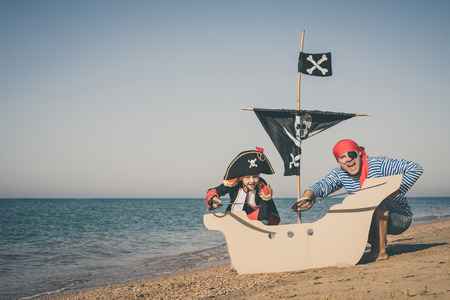 Father and son playing on the beach at the day time. They are dressed in sailor's vests and pirate costumes. Concept of happy game on vacation and friendly family. Standard-Bild - 116775455