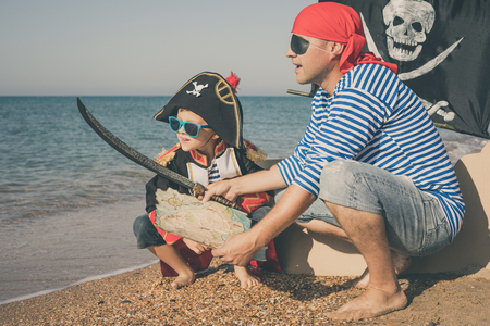 Father and son playing on the beach at the day time. They are dressed in sailor's vests and pirate costumes. Concept of happy game on vacation and friendly family. Standard-Bild - 116775456