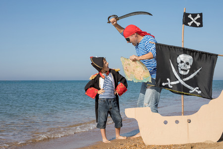 Father and son playing on the beach at the day time. They are dressed in sailor's vests and pirate costumes. Concept of happy game on vacation and friendly family. Standard-Bild - 116775460
