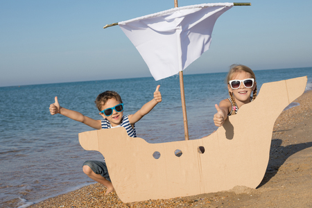 Happy children playing on the beach at the day time. Two Kids having fun outdoors. Concept of summer vacation and friendly family. Standard-Bild - 116775765