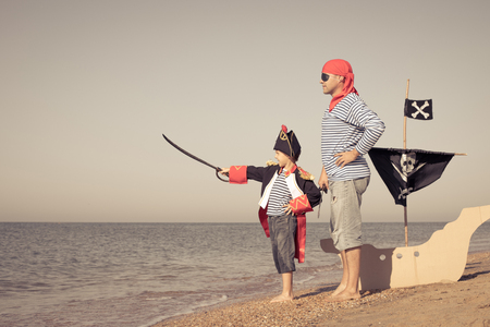 Father and son playing on the beach at the day time. They are dressed in sailor's vests and pirate costumes. Concept of happy game on vacation and friendly family. Standard-Bild - 116775767