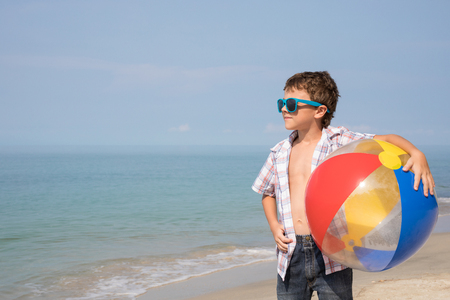 One happy little boy playing on the beach at the day time. Kid having fun outdoors. Concept of vacation. Standard-Bild - 116775770